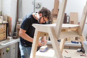 Furniture maker sharpening a chisel in his workshop