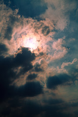 Sun behind clouds background