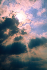 Sun behind clouds background