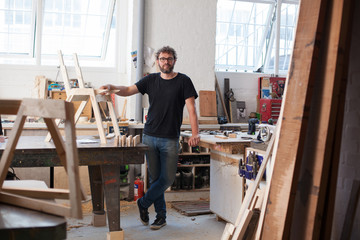 Environmental portrait of a furniture designer maker in his work