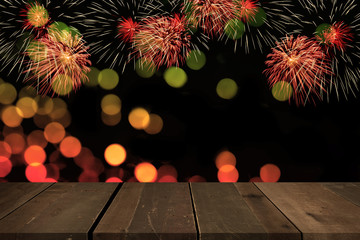 Fireworks blowing up in the sky with bokeh behind empty wooden table.