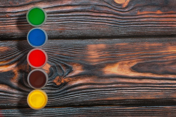 Set of colorful finger paint jars on a rustic background