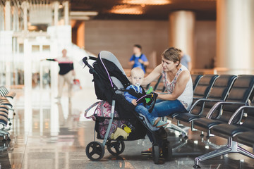 Mom and infant waiting for his flight at the airport