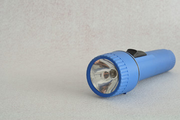 A blue plastic flashlight isolated against a white background