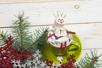 Christmas card with fun marshmallow snowman in green cup, tree
