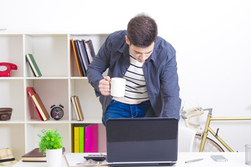 man typing of foot in the computer laptop with the cup of coffee in house or in the office