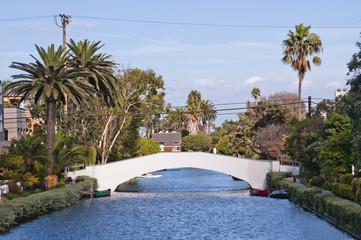 Frontal view of Venice Beach canal, with pedonal path and bridge in the backgruond, and palm trees and houses gardens on the side. It is an iconic destination for tourists visiting Los Angeles.