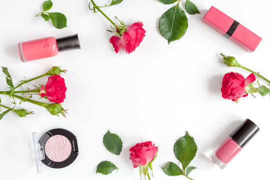 berry color decorative cosmetics with roses white background top view