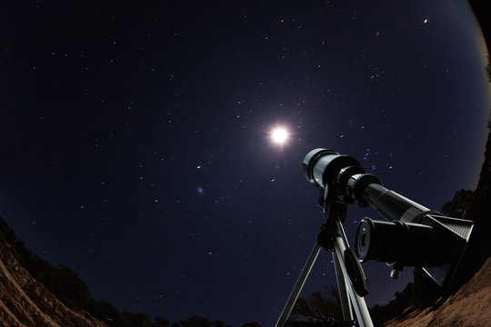 Telescope over night sky with stars and moon