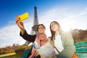 Two tourist taking selfie against the Eiffel Tower