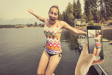 Taking a candid cell phone photo of a woman jumping off a dock at a beautiful lake during a fun summer vacation trip. The woman is showing lots of emotion and excitement as she jumps into the water