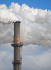 Vertical image of an old smokestack with smoke and steam billowing around. Copy space.
