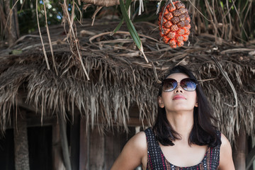 Portrait young woman relaxing with old wooden bungalow in beach