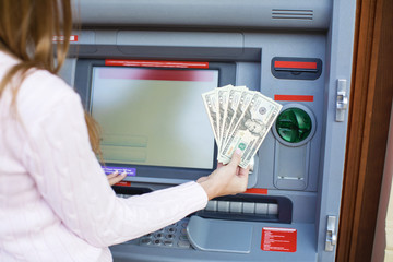 Woman hand withdrawing money from outdoor bank ATM