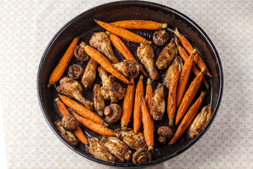 Roasted chicken wings with carrot and mushrooms on a tray