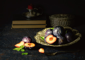 Still life with fresh plums placed in silver plate on dark background.