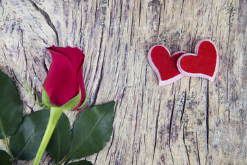 Red rose with two hearts on o;d textured wood for valentine's da
