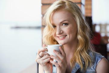 Beautiful girl drinking coffee in cafe