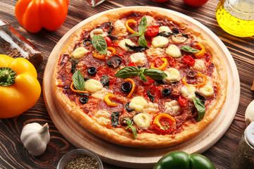 Freshly baked  pizza with ingredients on wooden table