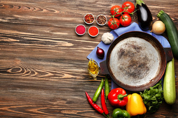 Iron frying pan with products on wooden background