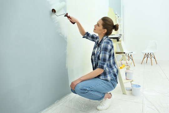 Beautiful young woman painting wall in room