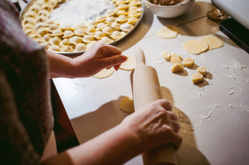 hand modeling dumplings at home in the kitchen. pelmeni lay on a baking sheet
