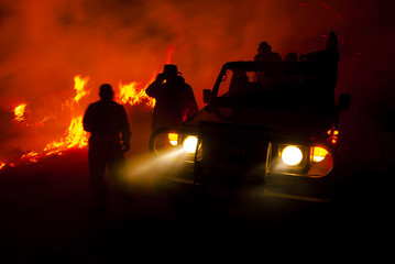 Fire fighters monitoring a controlled burn at night