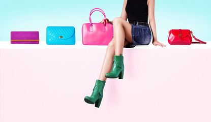 Many colorful bags purses with a woman wearing green boots. Shopping image.
