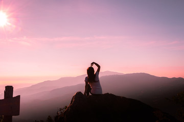 The silhouette of a woman Happy mountain morning sunrise.
