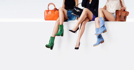 Many colorful woman shoes and bag accessories. 3 women sitting together on the white wall.