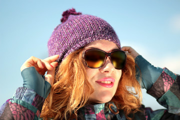 happy girl in colorful winter clothes and stylish sunglasses aga