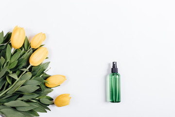 Green plastic bottle with water and a bouquet of yellow tulips o