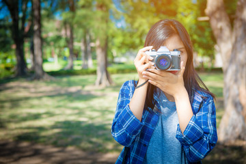 Portrait of happy Asian woman taking photos with a DSLR camera