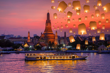 Wat arun and cruise ship in night time and floating lamp in yee peng festival under loy krathong day, Bangkok city ,Thailand