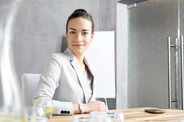 Fototapeta Bizneswoman. Kobieta pracownik biurowy siedzi przy stole konferencyjnym. obraz