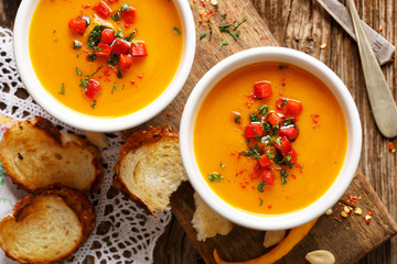 Homemade pumpkin soup in a white ceramic bowl on a wooden rustic table, nutritious and delicious vegetarian dish