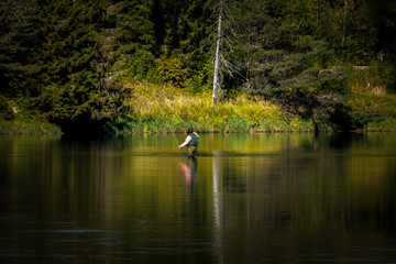 Man fly fishing standing in river, with green west.