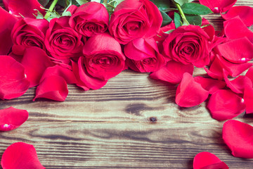 red roses in a bouquet and the scattered petals on a wooden background