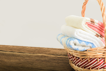 Bath towels of different colors in wicker basket