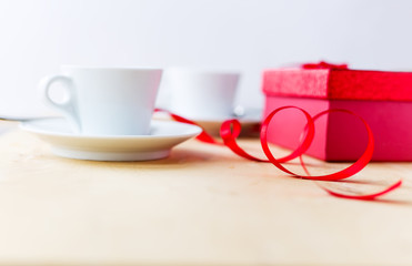 Cups with coffee, gift box, decorated by ribbon on wooden table.