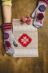 Gift package with ornament in hands at the girl. The composition settles down on a wooden background