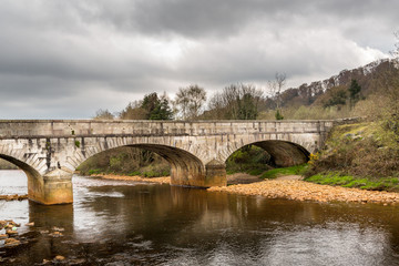 Old ancient stone bridge over calm river, beautiful Irish landscape. Scenic view.