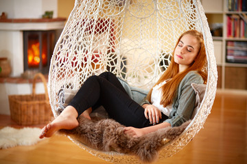 Young girl relaxing in a Hanging chair
