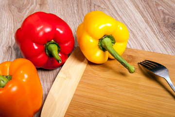 Three colors the peppers on wood cutting background with fork. Yellow, orange and red peppers. Popular pepper in kitchen.