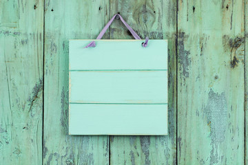 Blank mint green sign hanging by purple ribbon