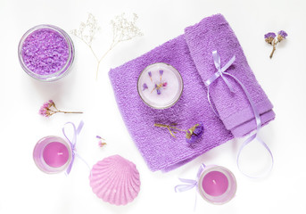 Spa products. Lavender bath salts, dry flowers, soap, cosmetic cream, candles and towel. Violet purple concept. Flat lay on white background, top view.