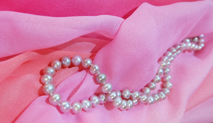 Beads from pearls against the background of pink fabric.