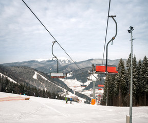 Happy skiers and snowboarders rising up on ski lift in the mountain winter resort