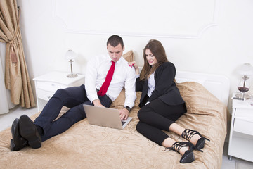 Business couple surfing the net while lying in bed. Business man and business woman using a laptop in hotel room.