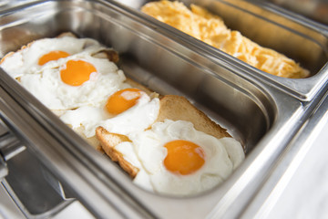 Catering buffet table with eggs and toast.